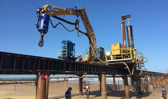The excavator runs over tracks to create the pipe line into the surf zone