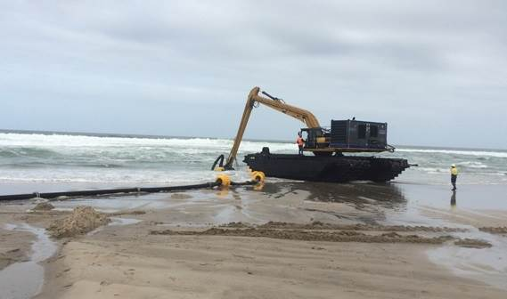 The DOP250 at work in the surf attached to an amphibious excavator